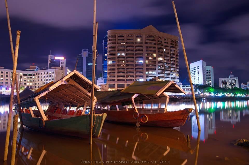 Photo Lights in the evening in downtown Kuching from across the waterfront.